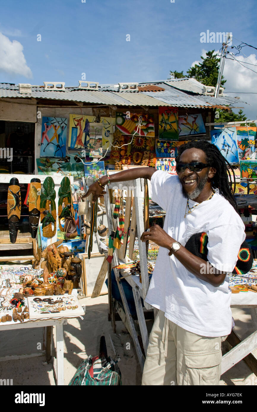 Jamaica Negril beach cool Rastafari man with souvenir shop - Stock Image