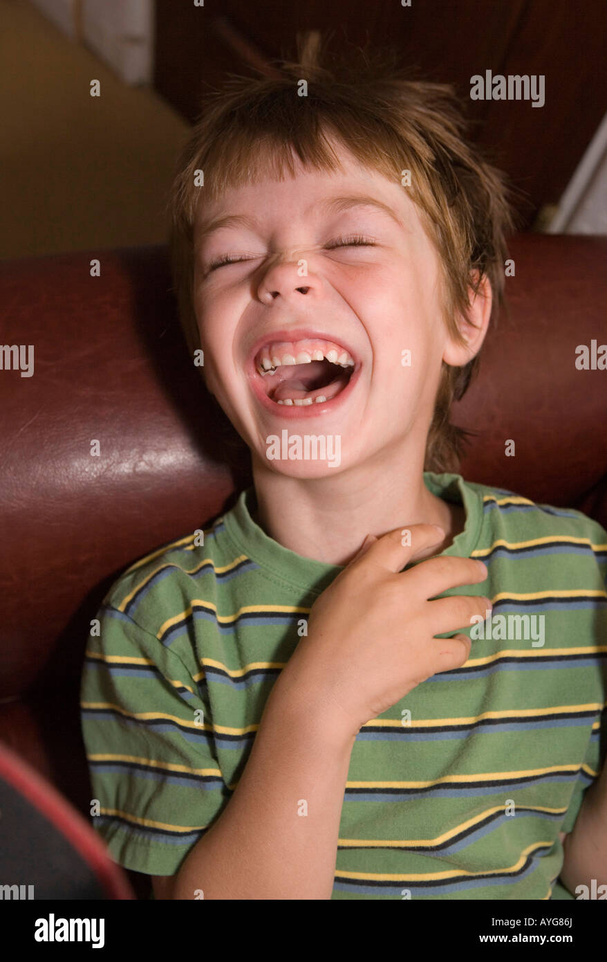 five year old boy laughing hard with mouth open - Stock Image