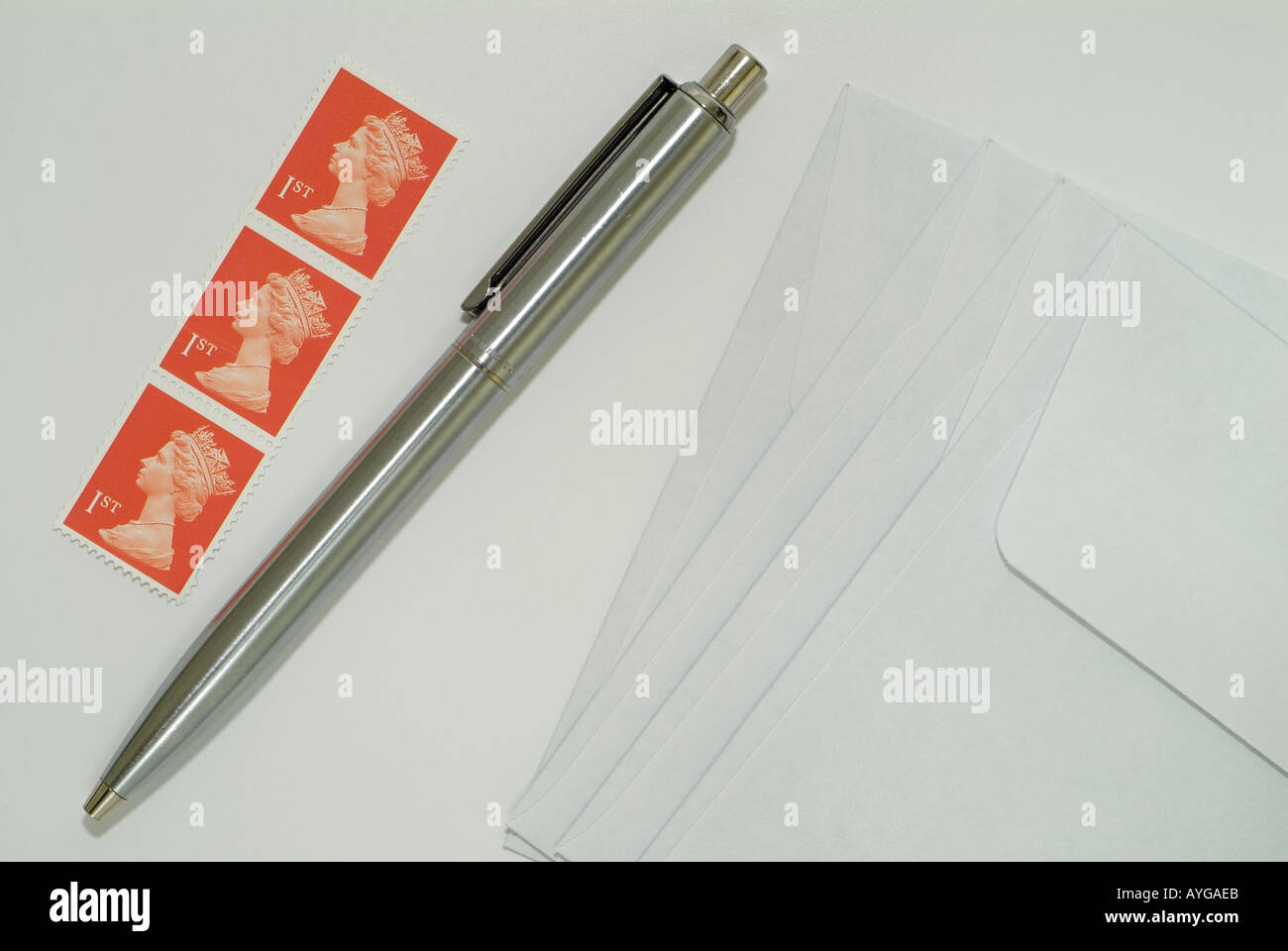 2c8275ba44e9 United Kingdom First Class Postage Stamps and Pen on Writing Paper Next to  Envelopes. -