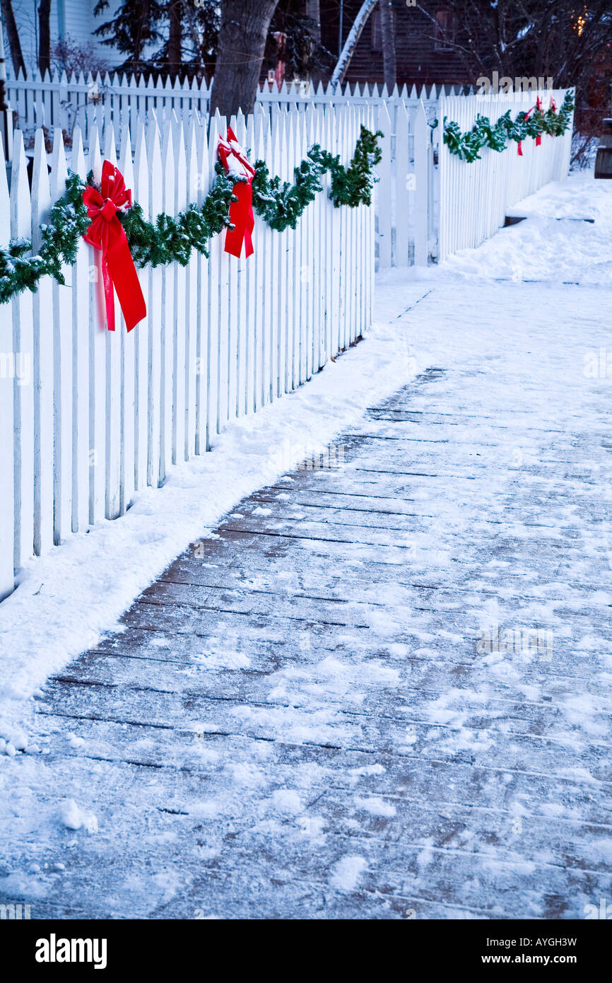 Christmas garland and red bows on a white picket fence - Stock Image