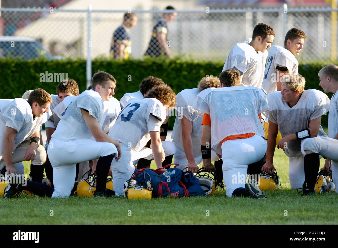 Football players plan with coaches before playing in a game - Stock Image