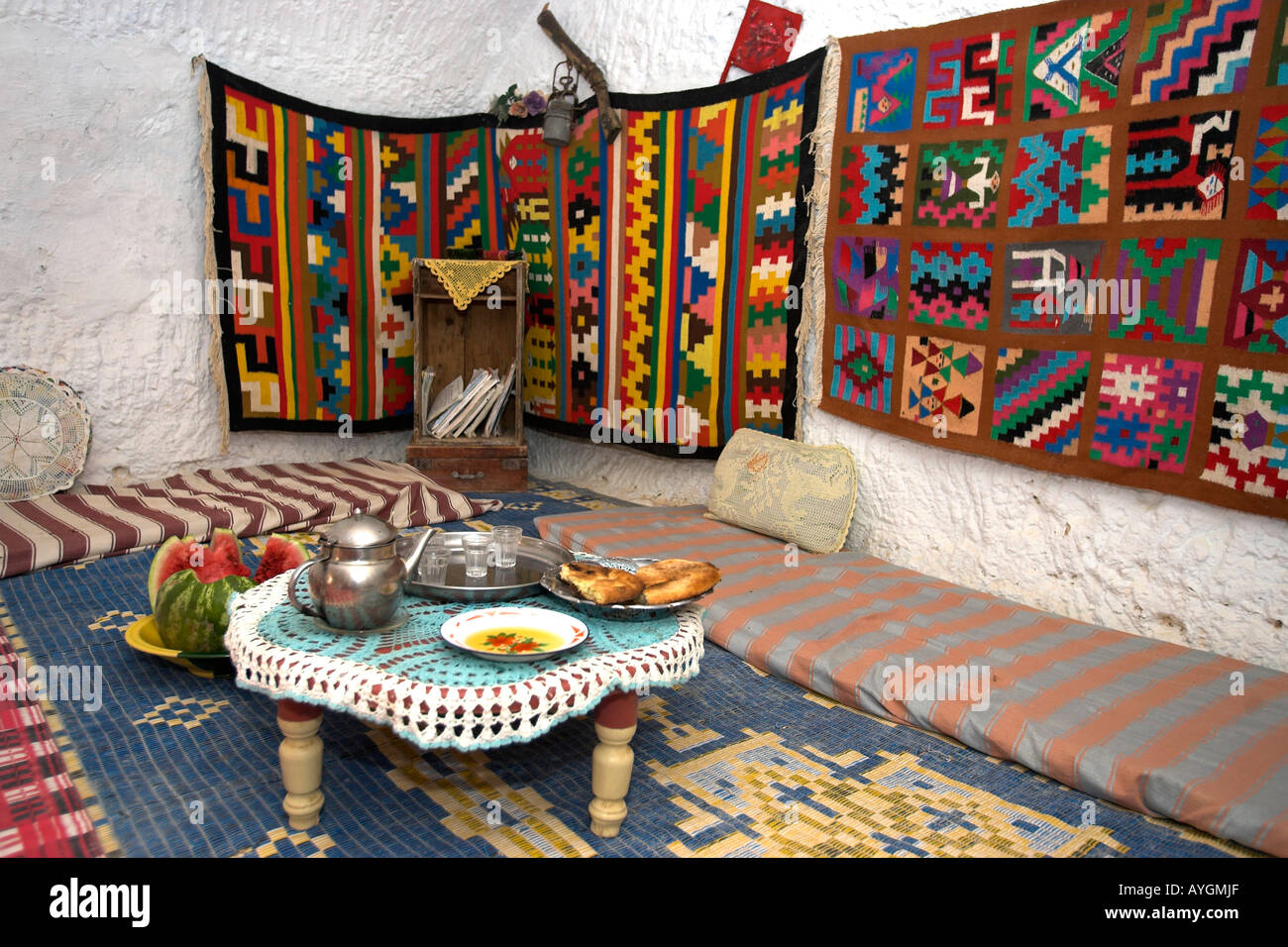 Tea bread and fruit set out for visitor in underground Berber troglodyte home with colourful wall hangings Matmata Stock Photo