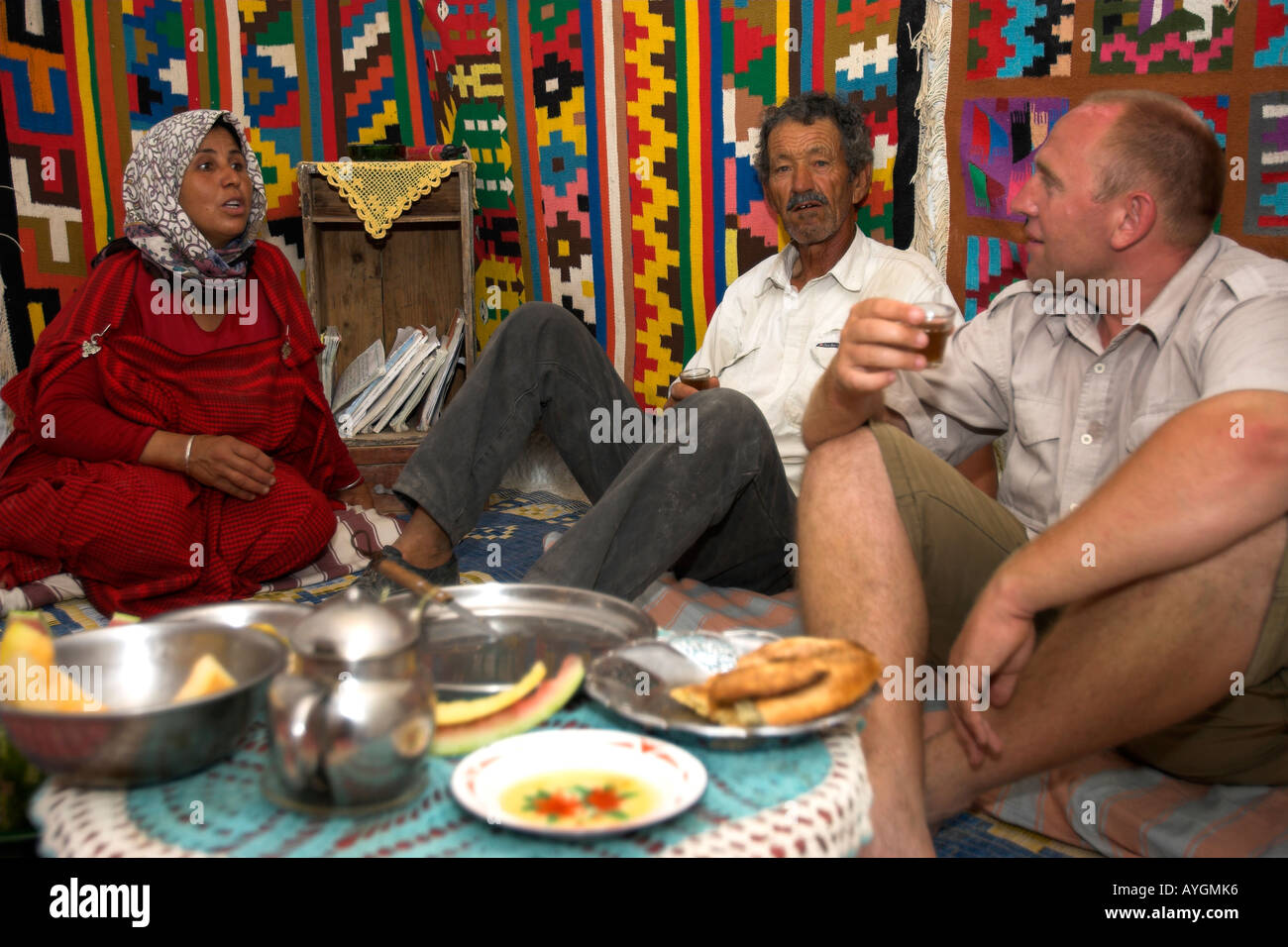 Visitor seated on floor dining with Berber family underground troglodyte home Matmata Tunisia Stock Photo