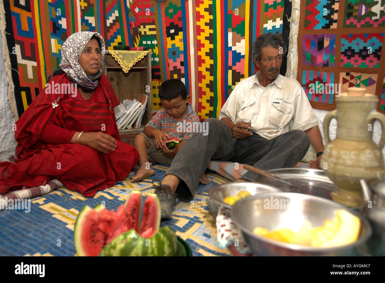 Woman entertains with husband and child in her underground Berber troglodyte cave home Matmata Tunisia Stock Photo