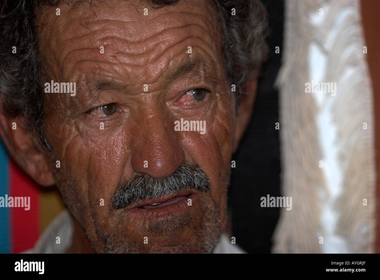Unshaved Berber man with moustache underground troglodyte family home Matmata Tunisia - Stock Image