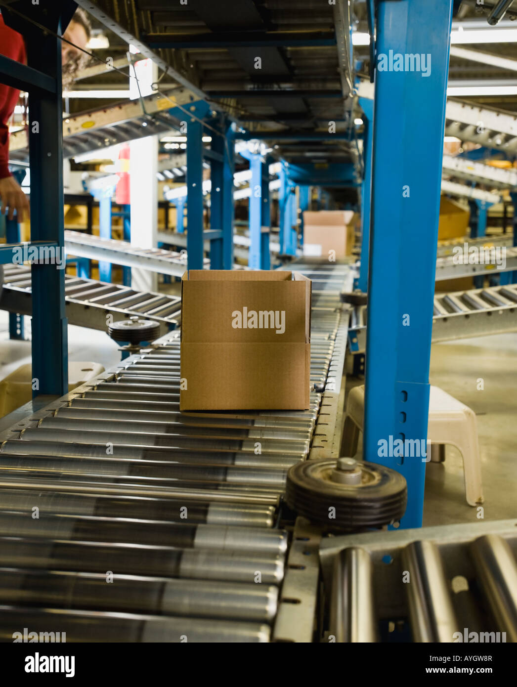 Boxes on conveyor belt in warehouse - Stock Image