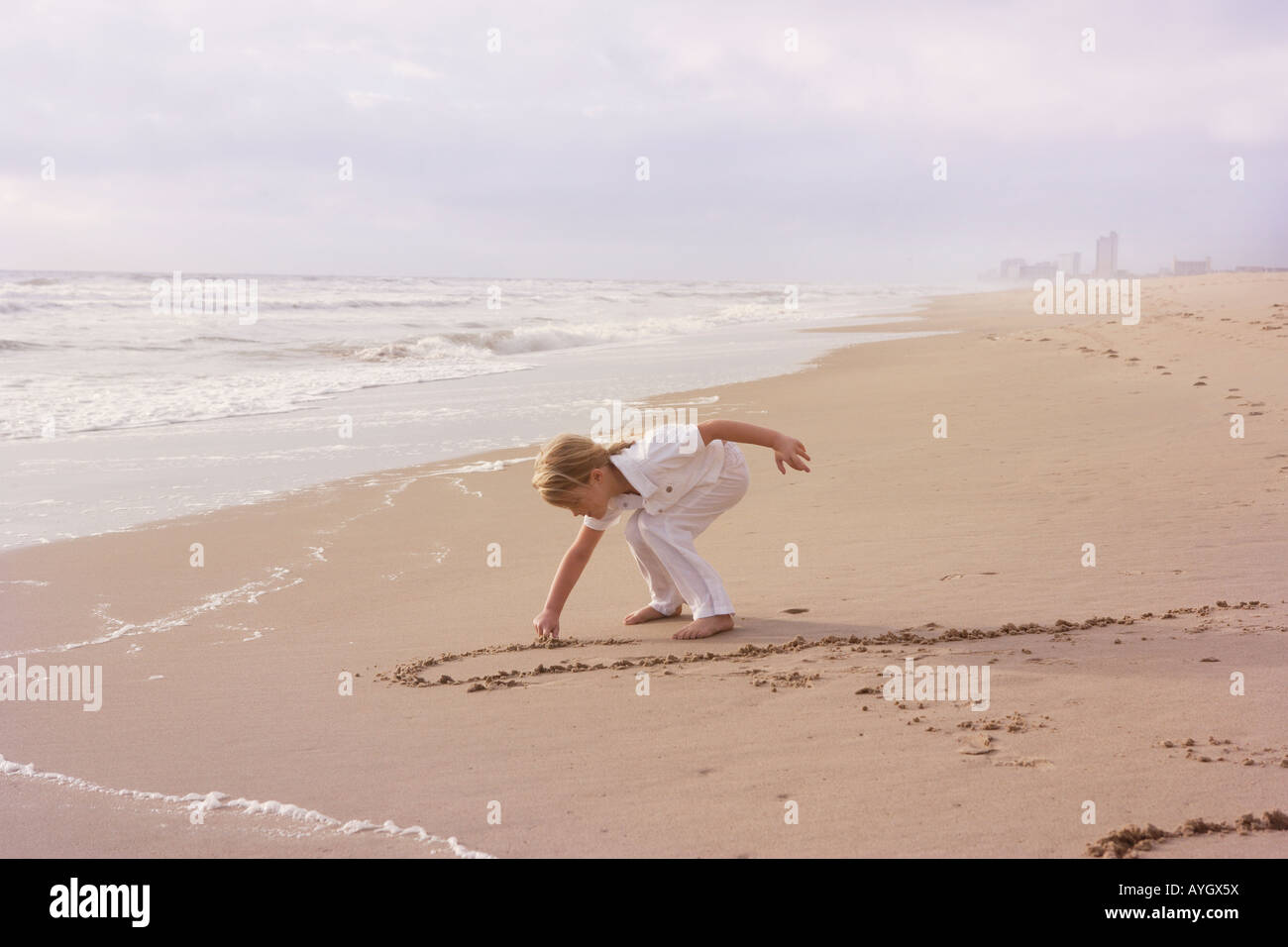 Girl drawing in sand - Stock Image