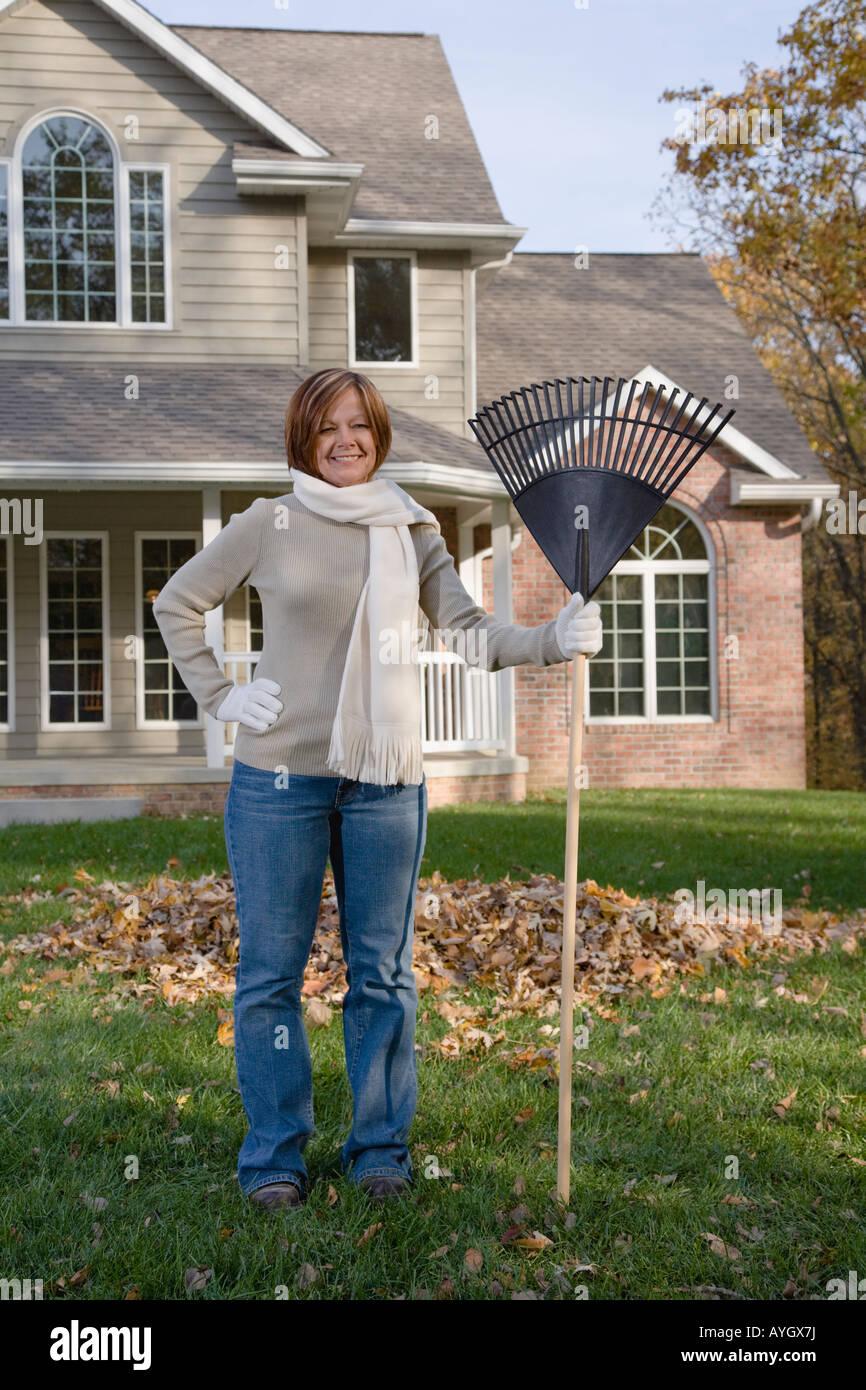 Woman holding rake in yard - Stock Image