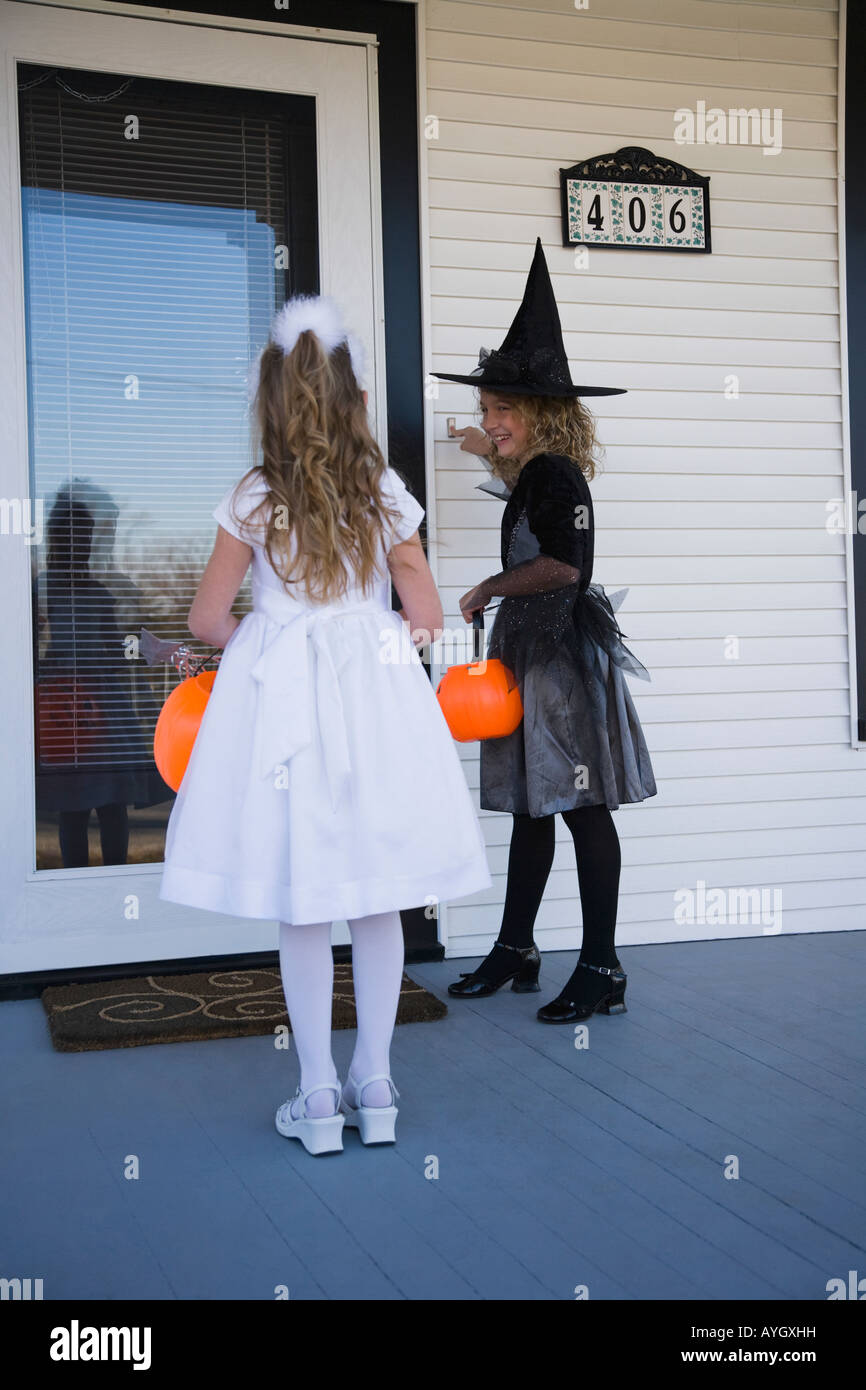 Girls in wtich and princess Halloween costumes trick or treating - Stock Image