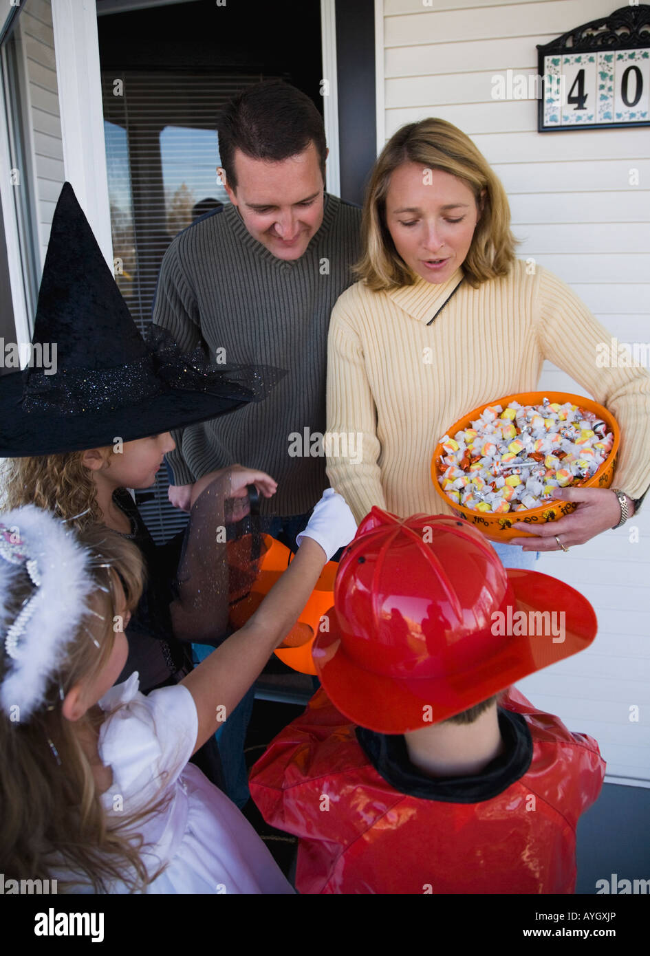 Children in Halloween costumes trick or treating - Stock Image