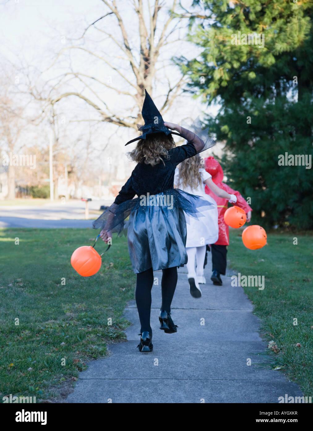 Children in Halloween costumes skipping on sidewalk - Stock Image