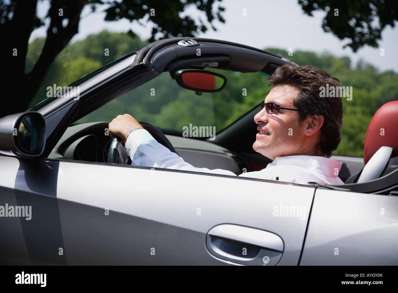 Man driving convertible car - Stock Image