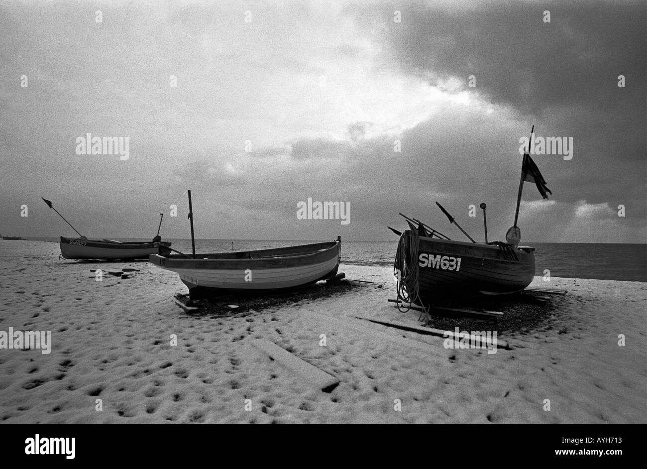 Fishing boats dusted with snow on Brighton beach - Stock Image