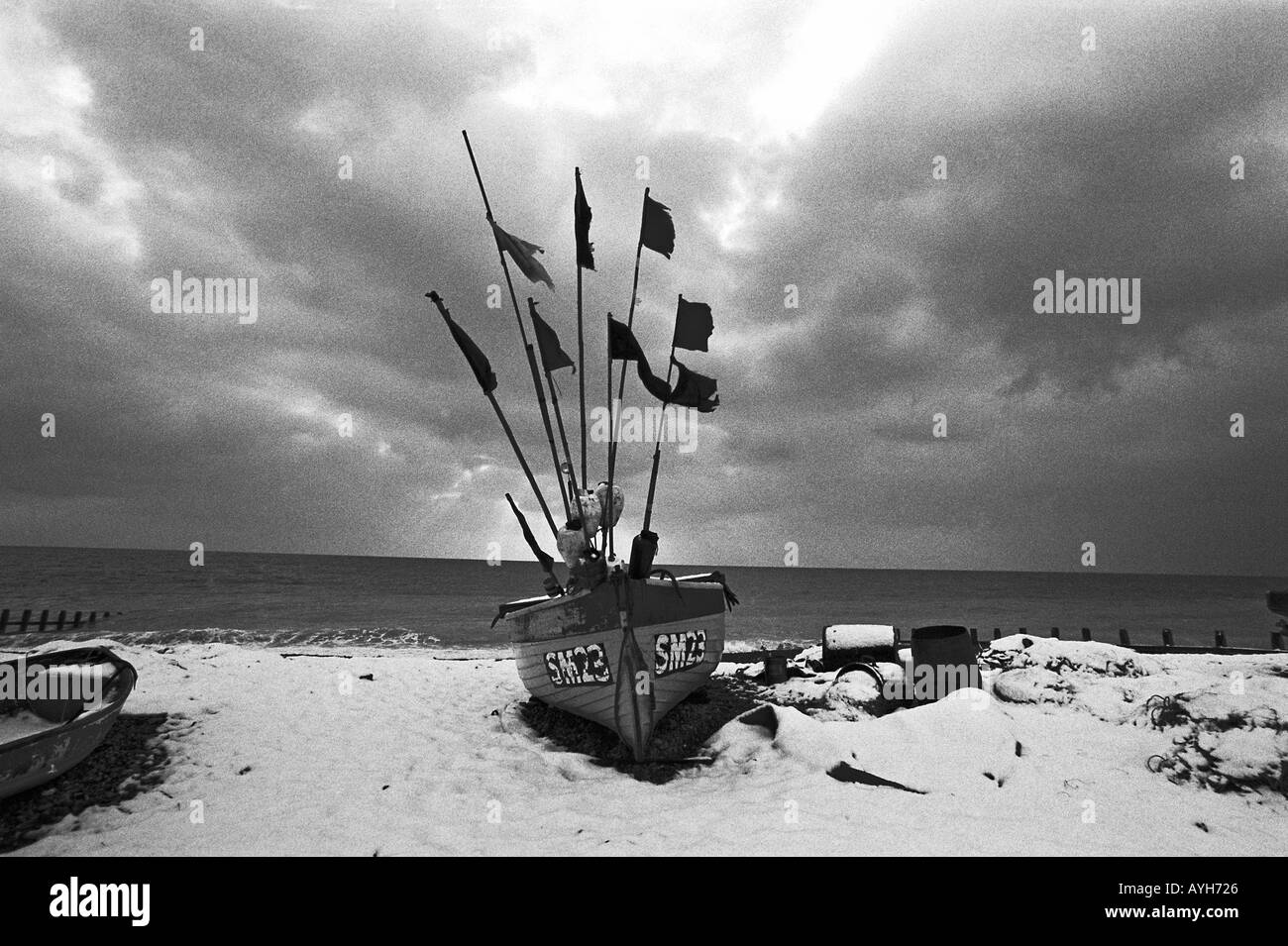 A fishing boat dusted with snow on Brighton beach - Stock Image