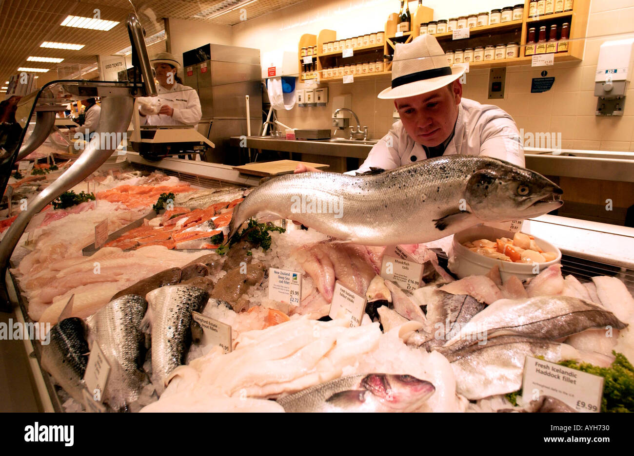 A fishmonger in uniform and hat at Waitrose Britains leading quality supermarket - Stock Image