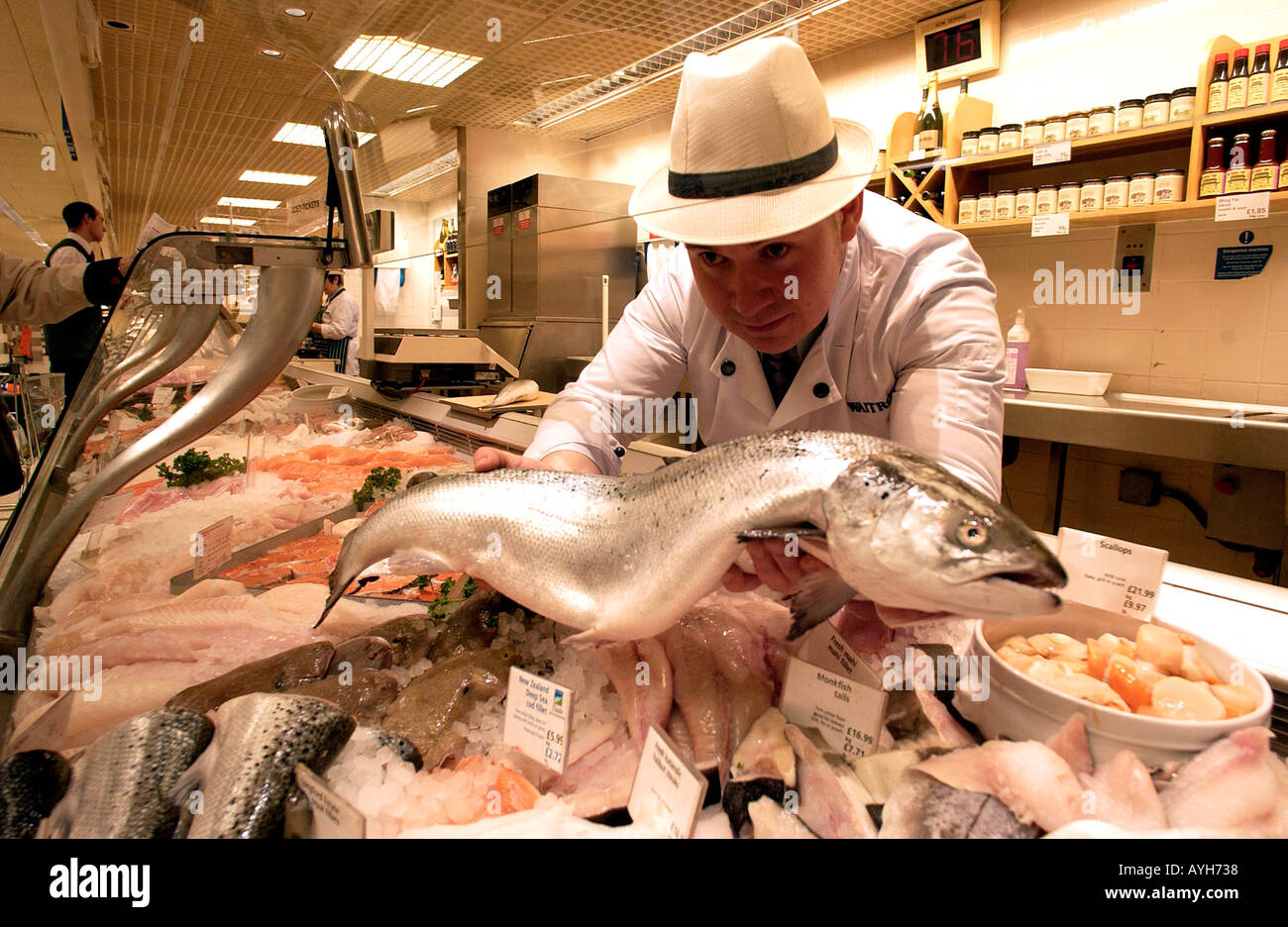 A fishmonger in uniform and hat displays a fish at Waitrose Britains leading quality supermarket - Stock Image