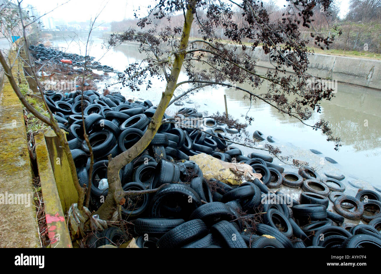 Discarded car tyres dumped in a London waterway. - Stock Image