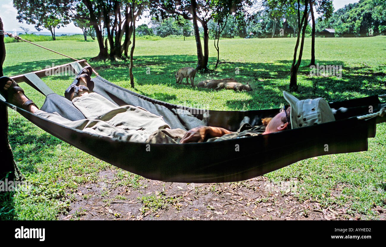 AFRICA KENYA MASAI MARA RESERVE KICHWA TEMBA Tourist asleep in hammock outside tents of Kichua Temba Safari Camp - Stock Image