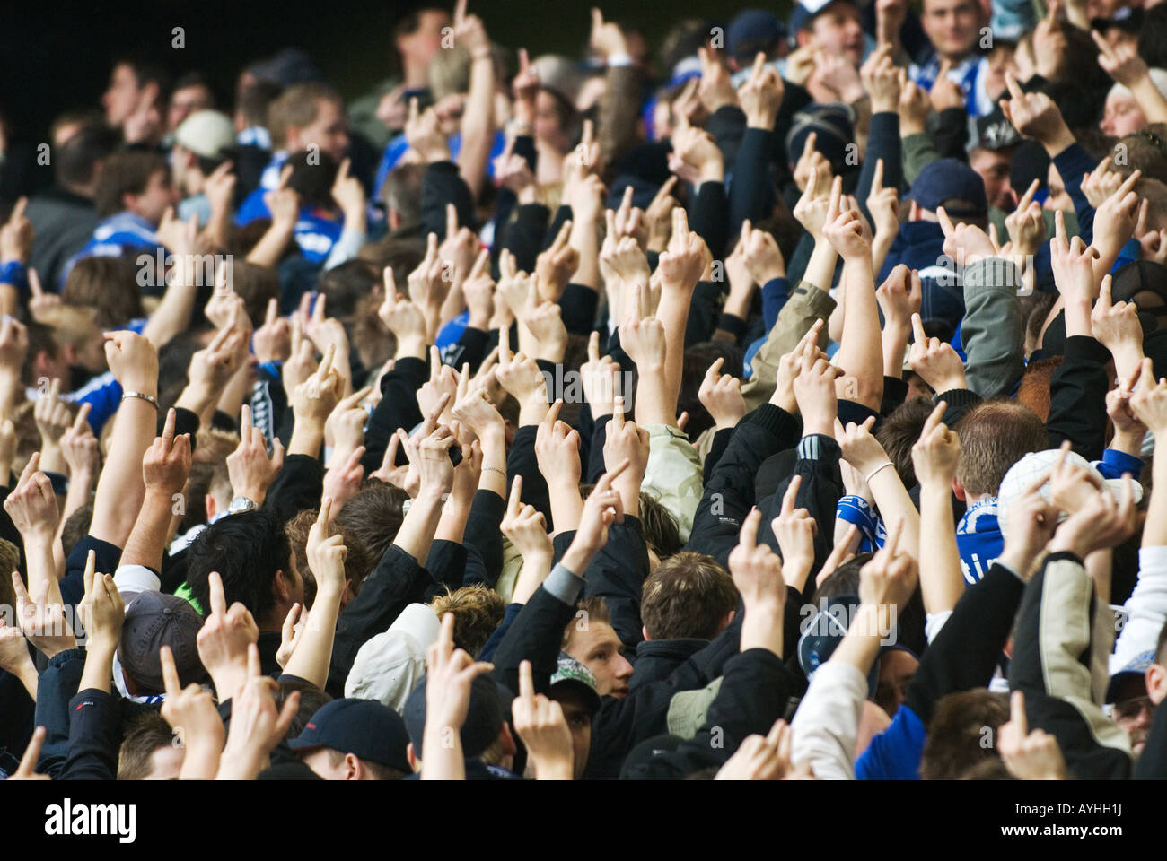 football fans of Schalke 04 show their outstreched middle fingers to the opposing team - Stock Image