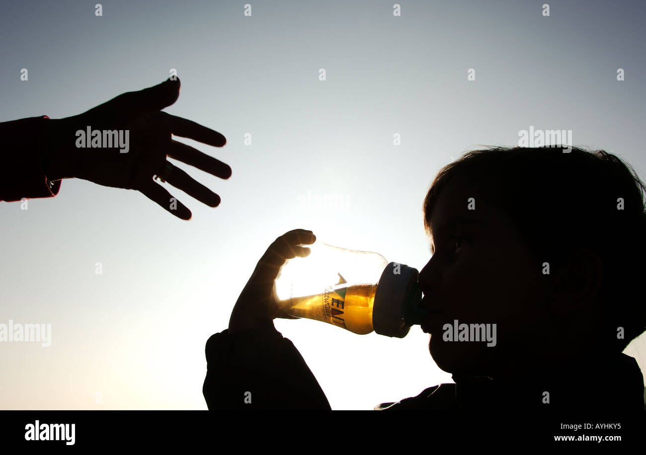 Toddler drinking from bottle while hand of parent reaches out - Stock Image