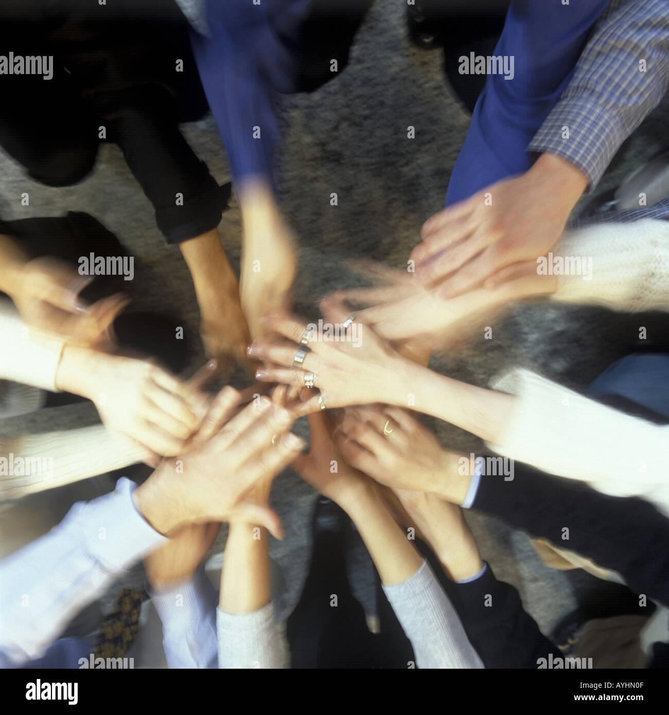 Menschen stehen im Kreis und strecken die Haende zur Mitte - Stock Image