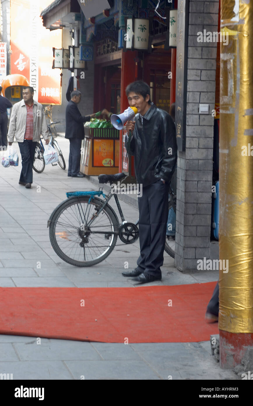Shopkeeper using a megaphone to advertise his shop in Old Beijing China - Stock Image