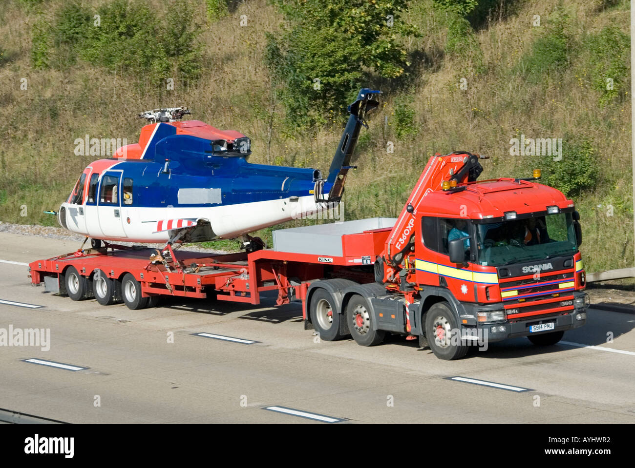 M25 motorway helicopter fuselage on low loader trailer behind Scania lorry - Stock Image