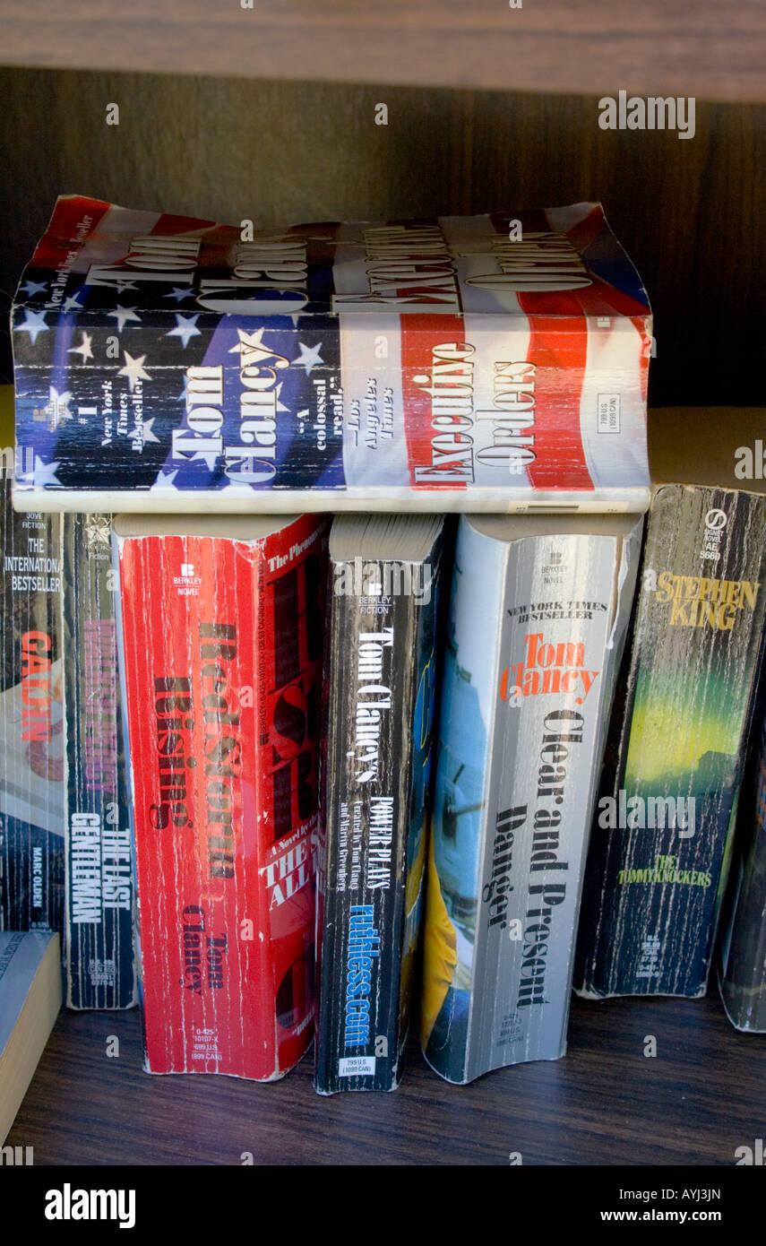 Well read Tom Clancy paperbacks on bookshelf. St Paul Minnesota USA - Stock Image