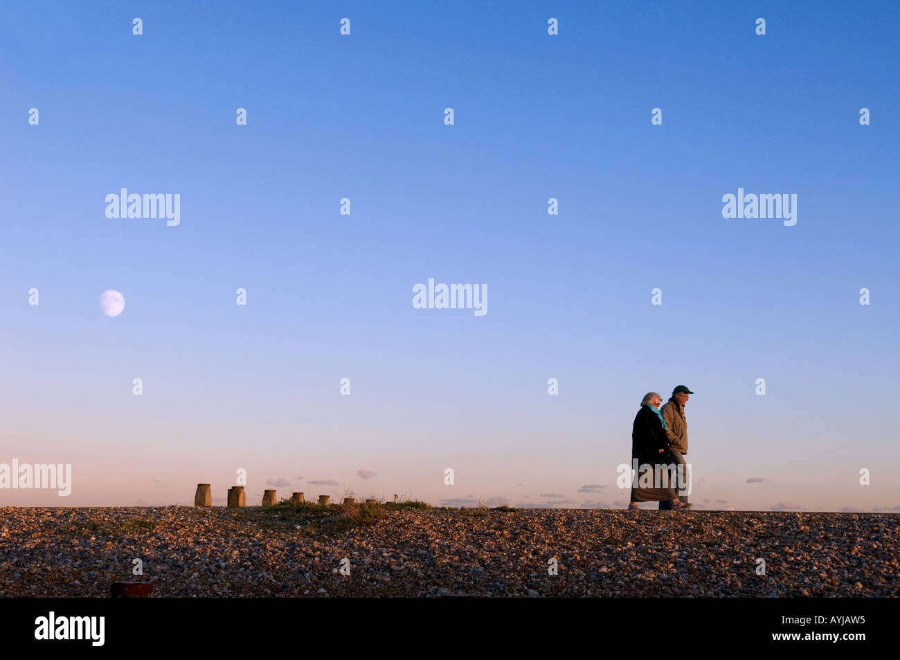 The moon rising above a couple as they walk along Eastbourne seafront at dusk. Picture by Jim Holden. - Stock Image