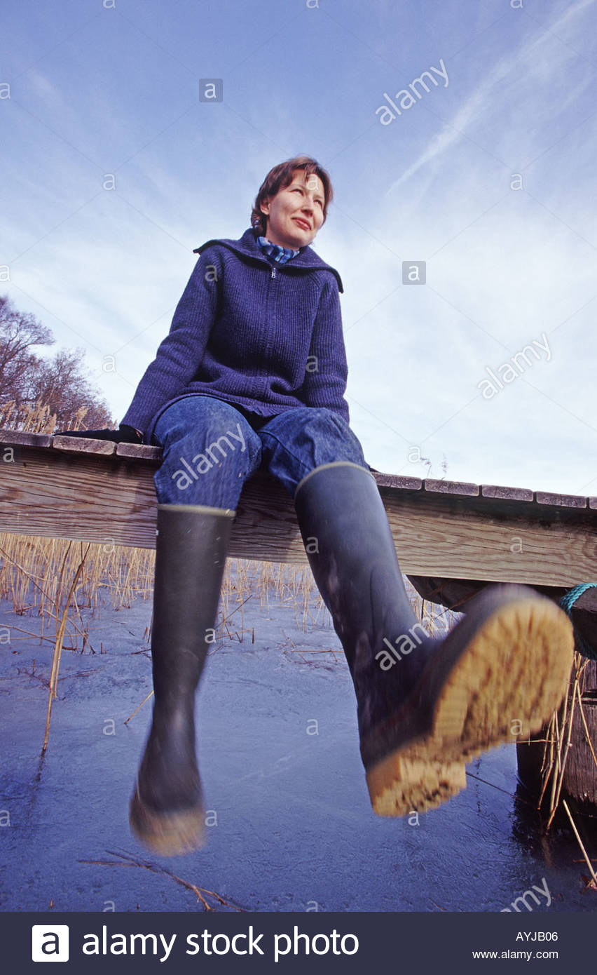 A Woman Wearing Rubber Boots Sitting On A Bridge