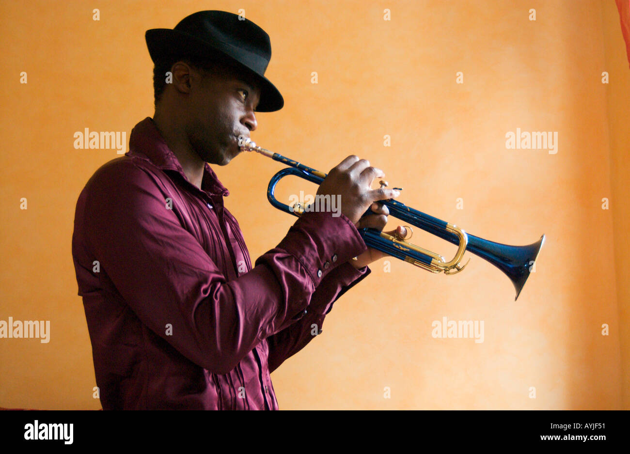 african american man wearing a fedora hat plays a blue Trumpet in front of a yellow wall inside - Stock Image