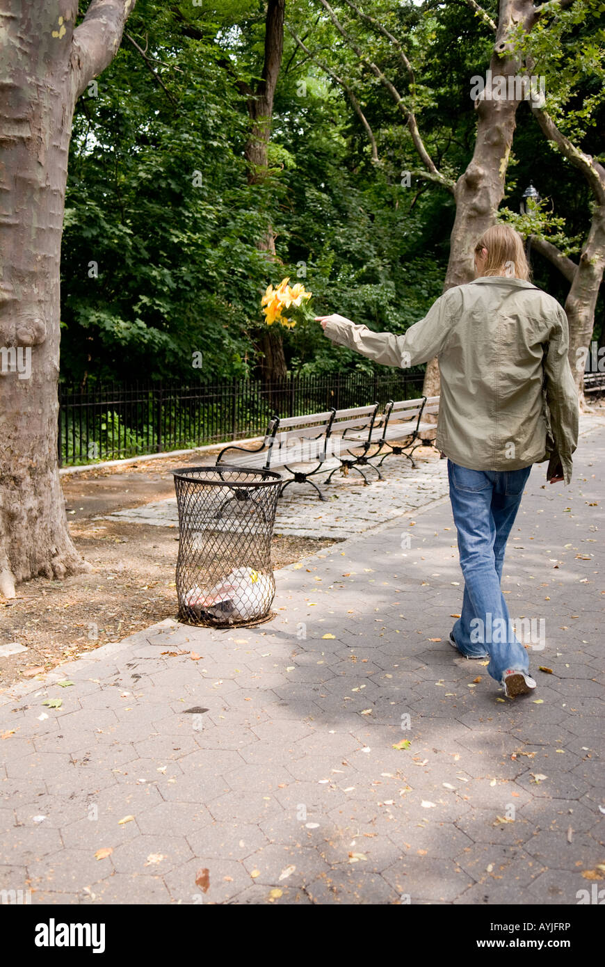 young Caucasian boy disheartened throwing away flowers - Stock Image