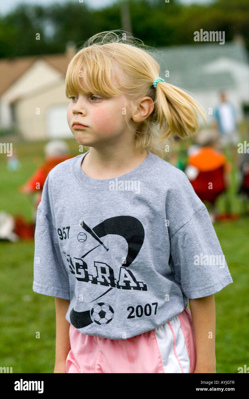 Intense sensitive girl age 7 soccer player waiting to enter game. Carondelet Field by Expo School St Paul Minnesota - Stock Image