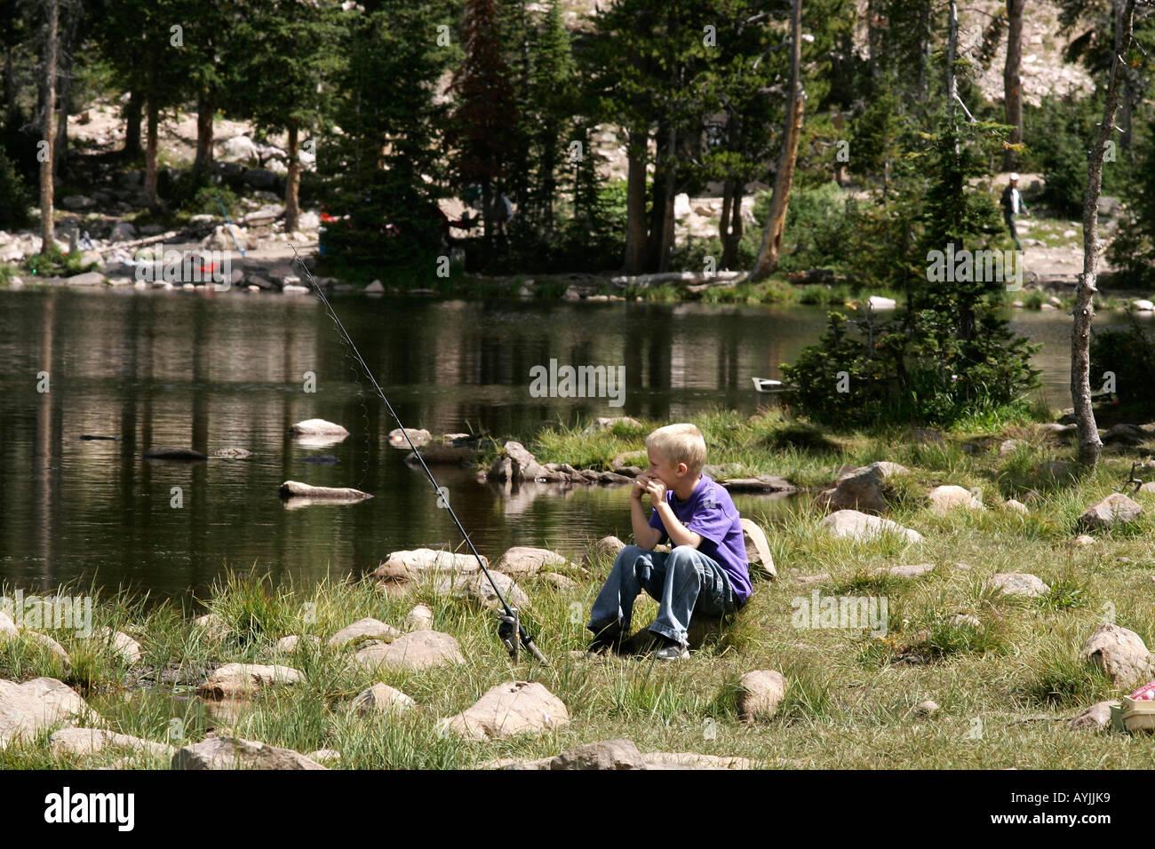Young boy fishing on a High mountain lake, high Uintahs, Utah Aug 2005 - Stock Image