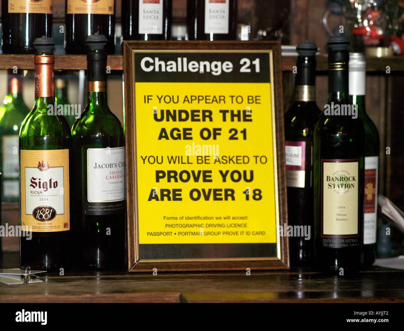 Sign at Bar Prohibiting Underage Drinking And Bottles Of Wine - Stock Image