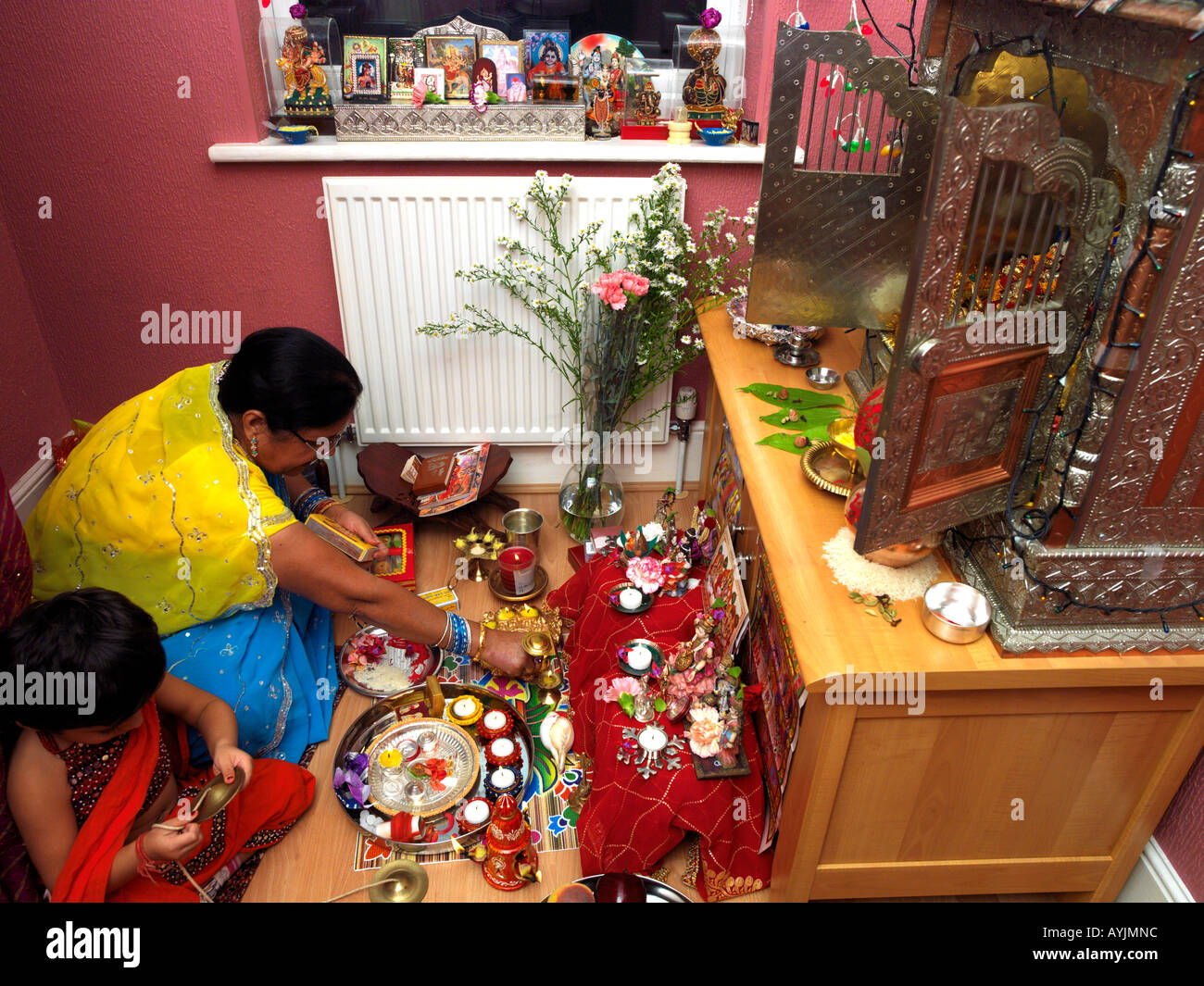Family Worshipping At Home With Grandmother Lighting Lamps At Diwali  Celebrations At Home Tooting London England
