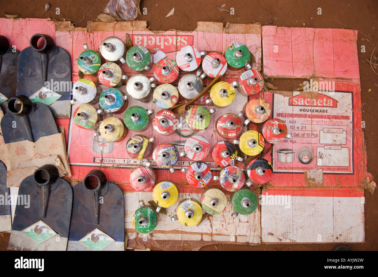 Cluster of home made oil lamps made of recycled cans and shovels on the market . Mozambique - Stock Image