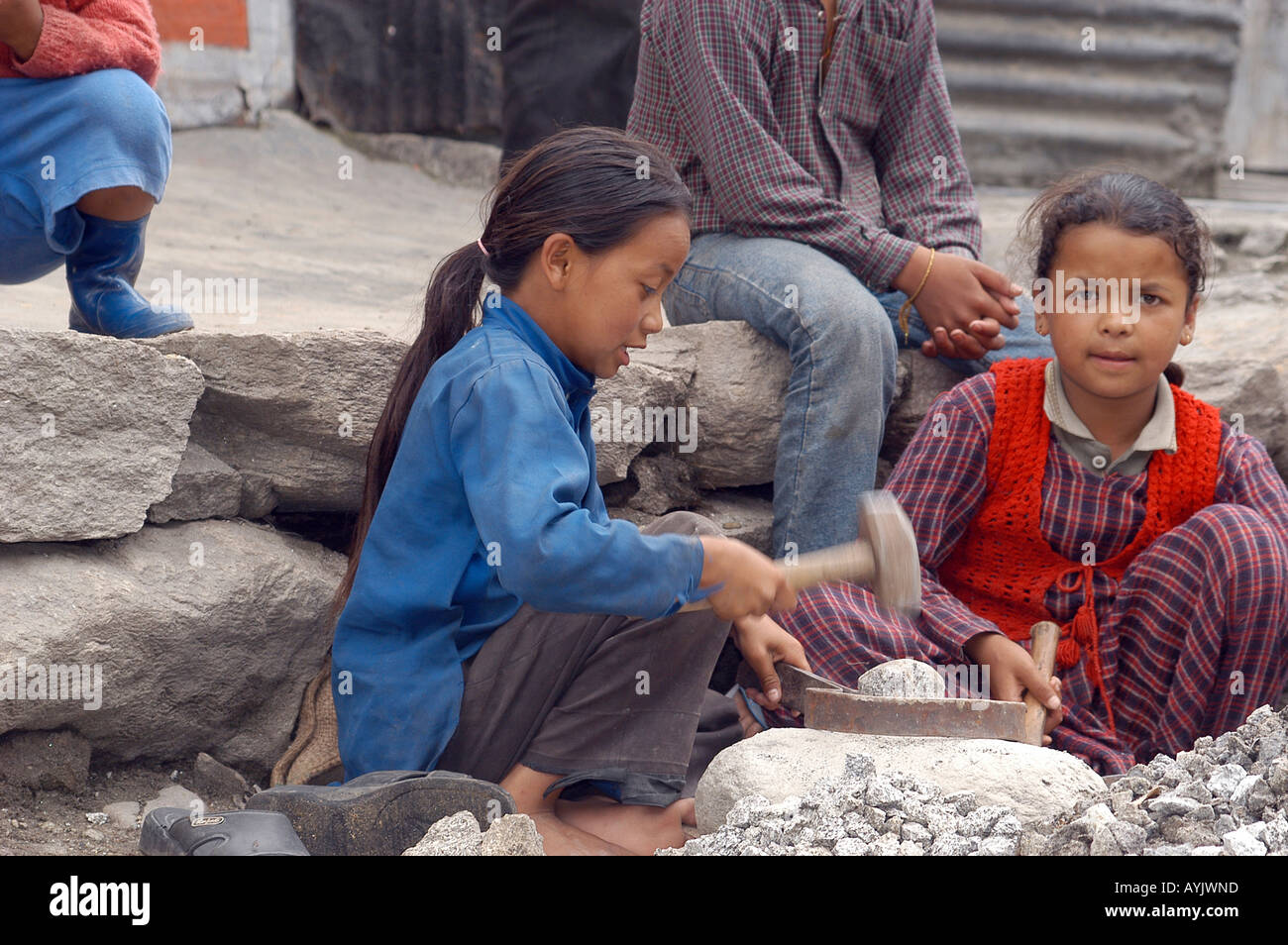young children of about 8 years old at work at a stone quarry breaking rocks into gravel - Stock Image