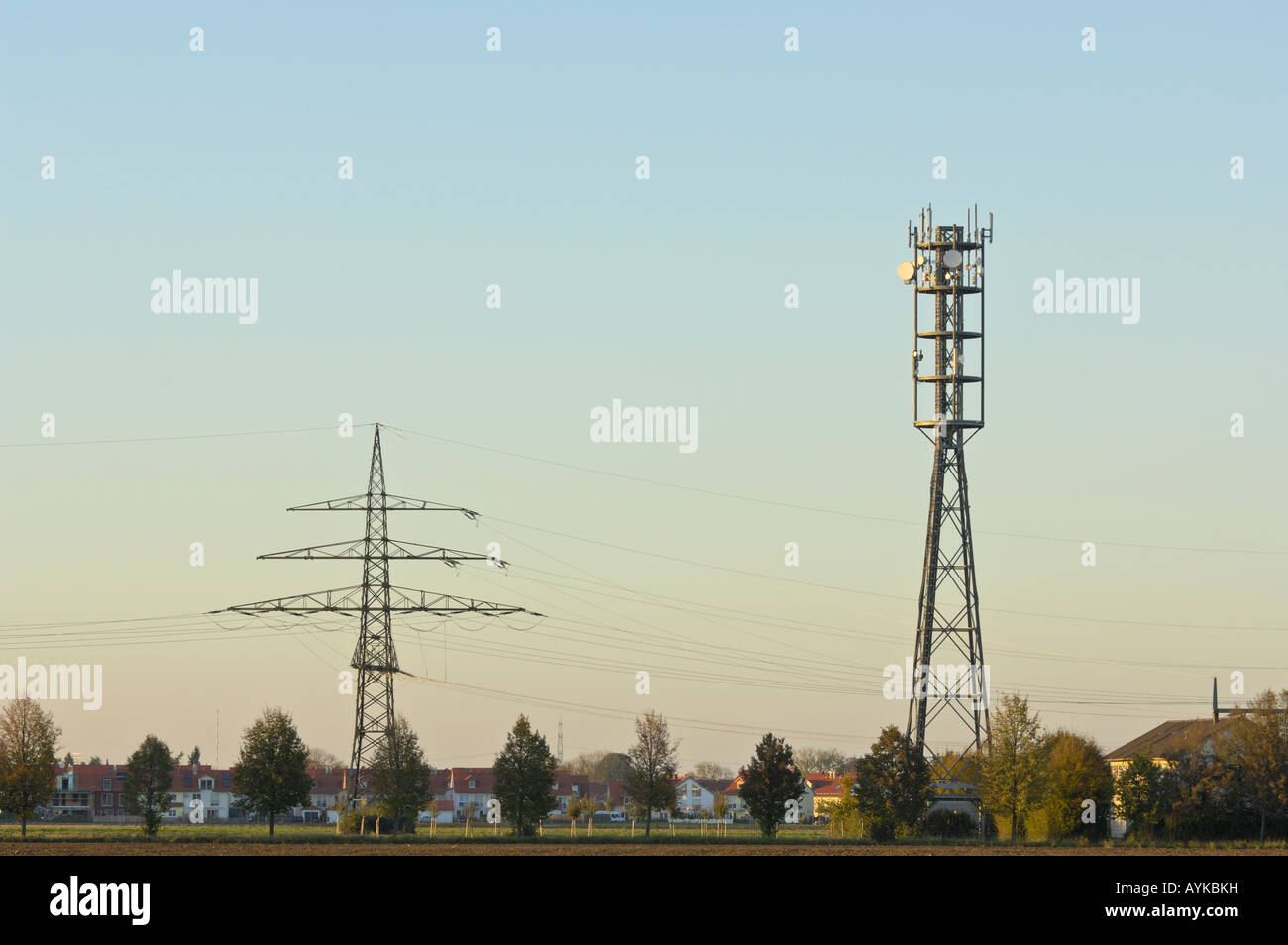 Electric smog A radio tower and a high voltage power line near a village in Bavaria, Germany - Stock Image