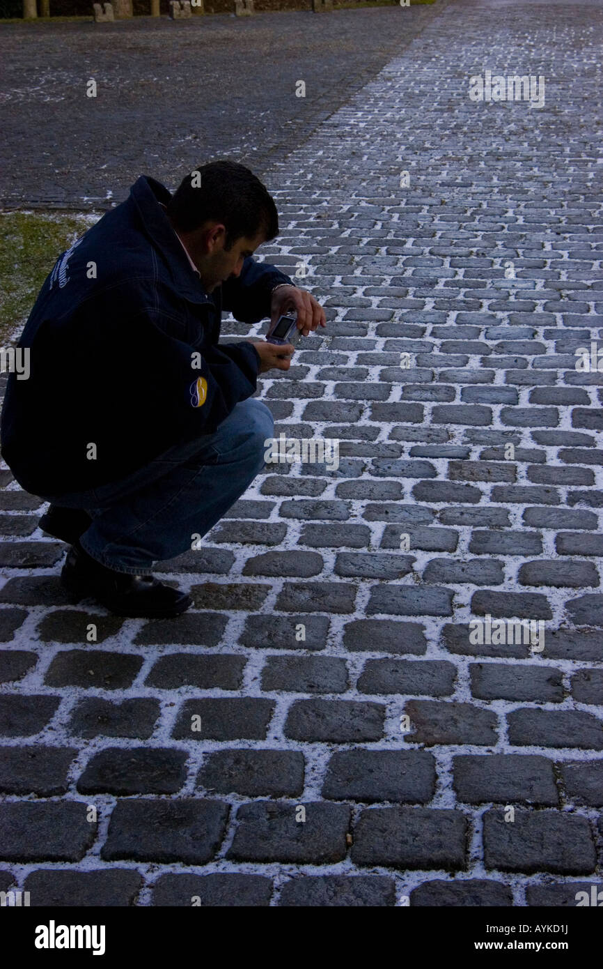 an amateur photographer take a few photos of the snow between the bricks of an old road, in Hausmening, Austria - Stock Image