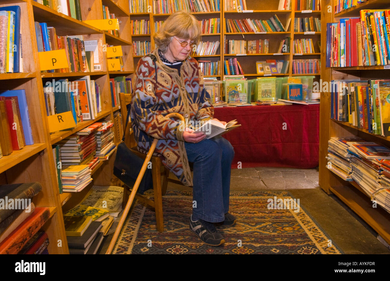 Woman browsing book at Richard Booths Bookshop Hay on Wye Powys Wales UK EU the World's largest secondhand bookshop - Stock Image