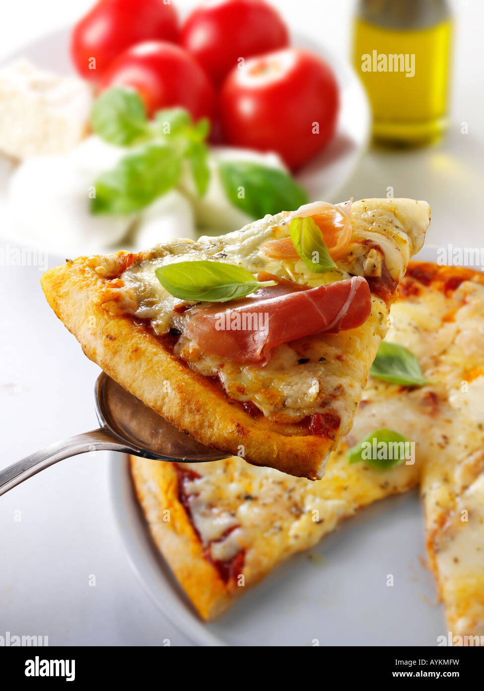 Pizza slice topped with prosciutto or Parma ham - Stock Image
