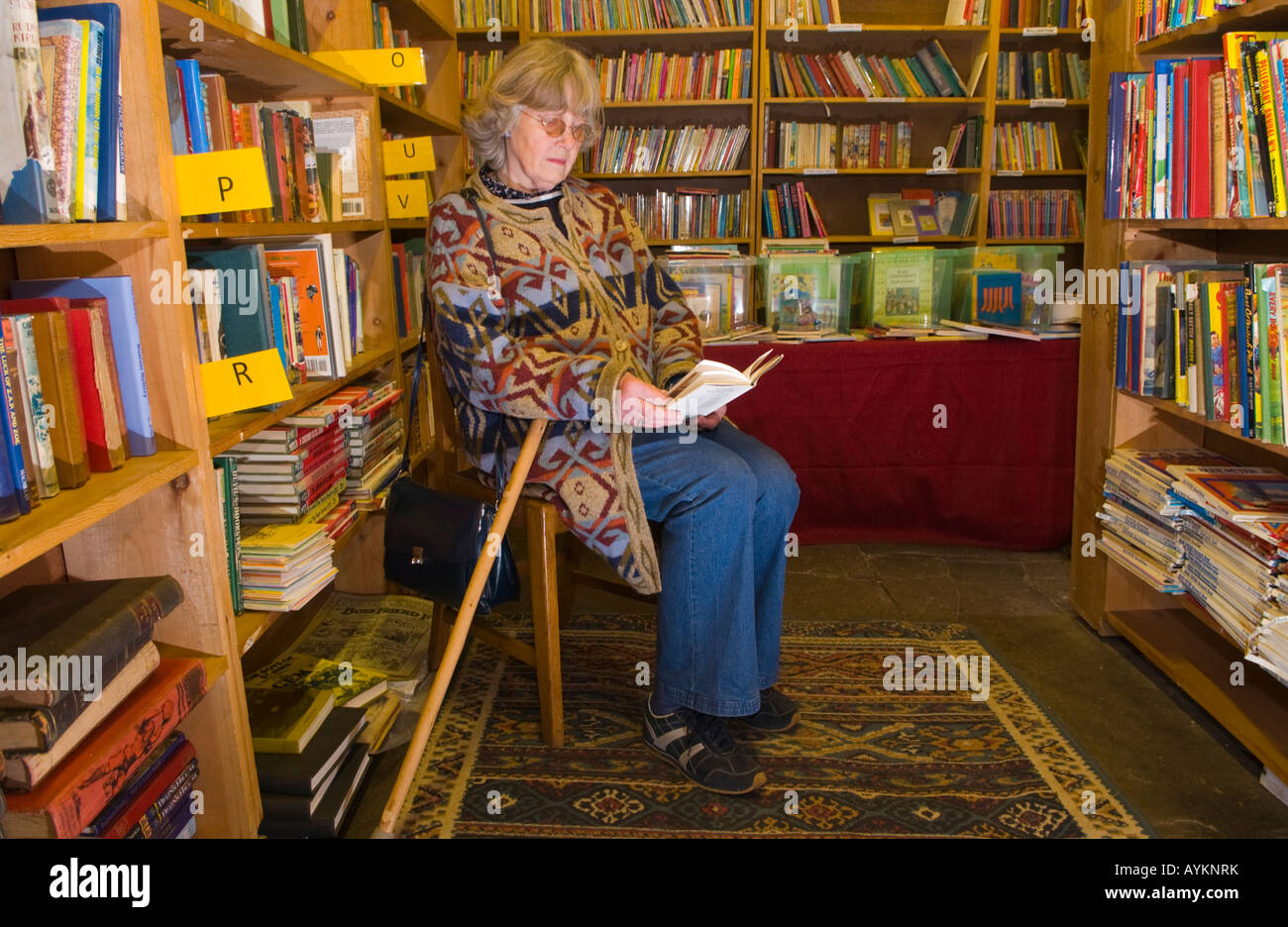 Woman browsing thru book at Richard Booths Bookshop Hay on Wye Powys Wales UK EU the World's largest secondhand - Stock Image