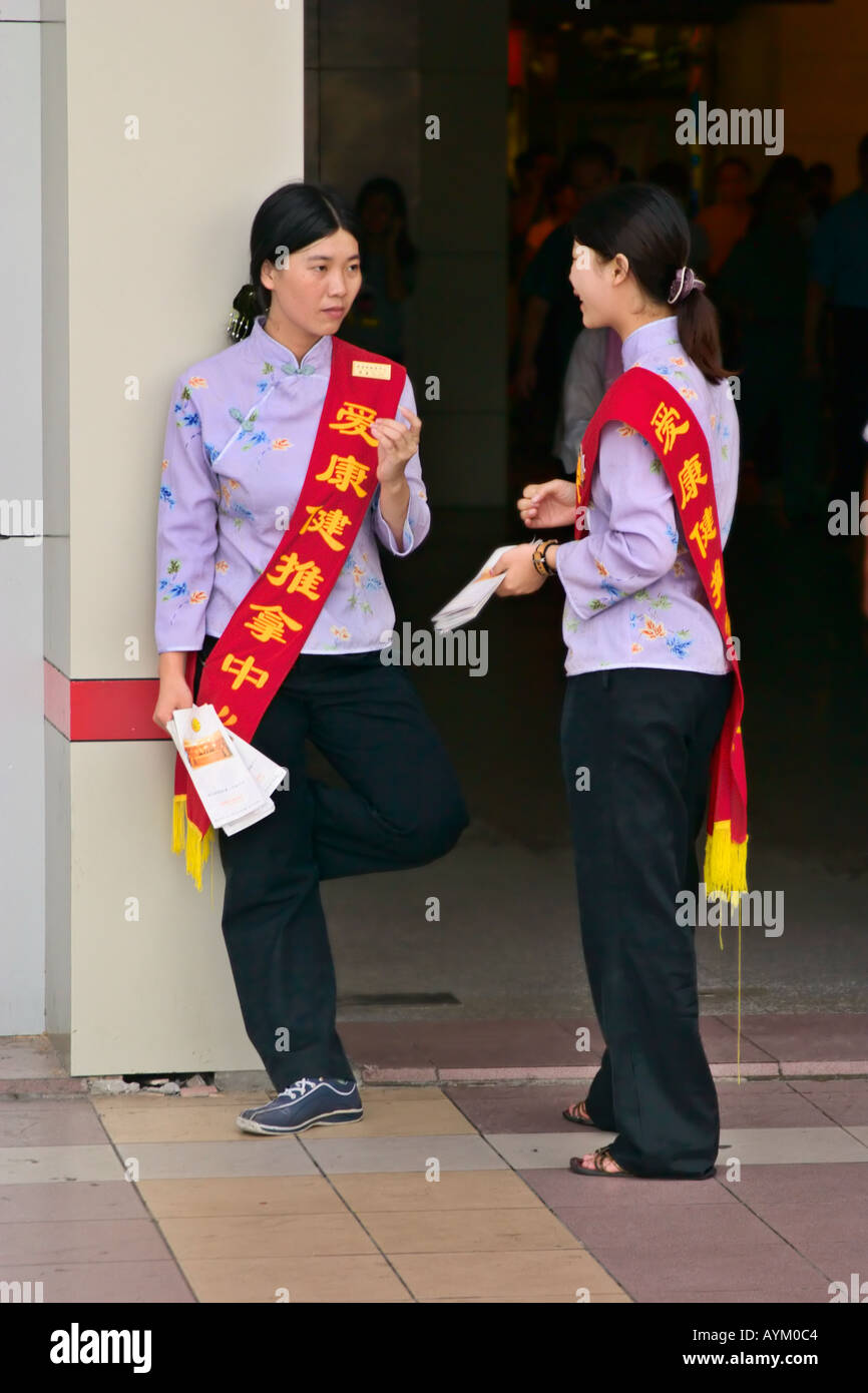 Two women promoters chatting on a street corner Shenzhen China - Stock Image