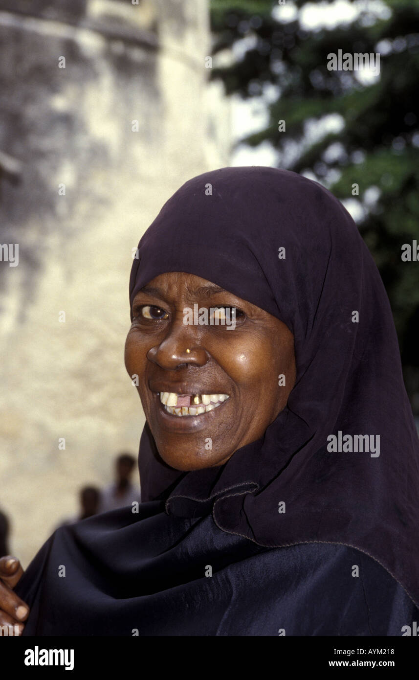 A woman of Lamu wearing black buibui head and body covering or cloak Lamu island Kenya coast East Africa - Stock Image