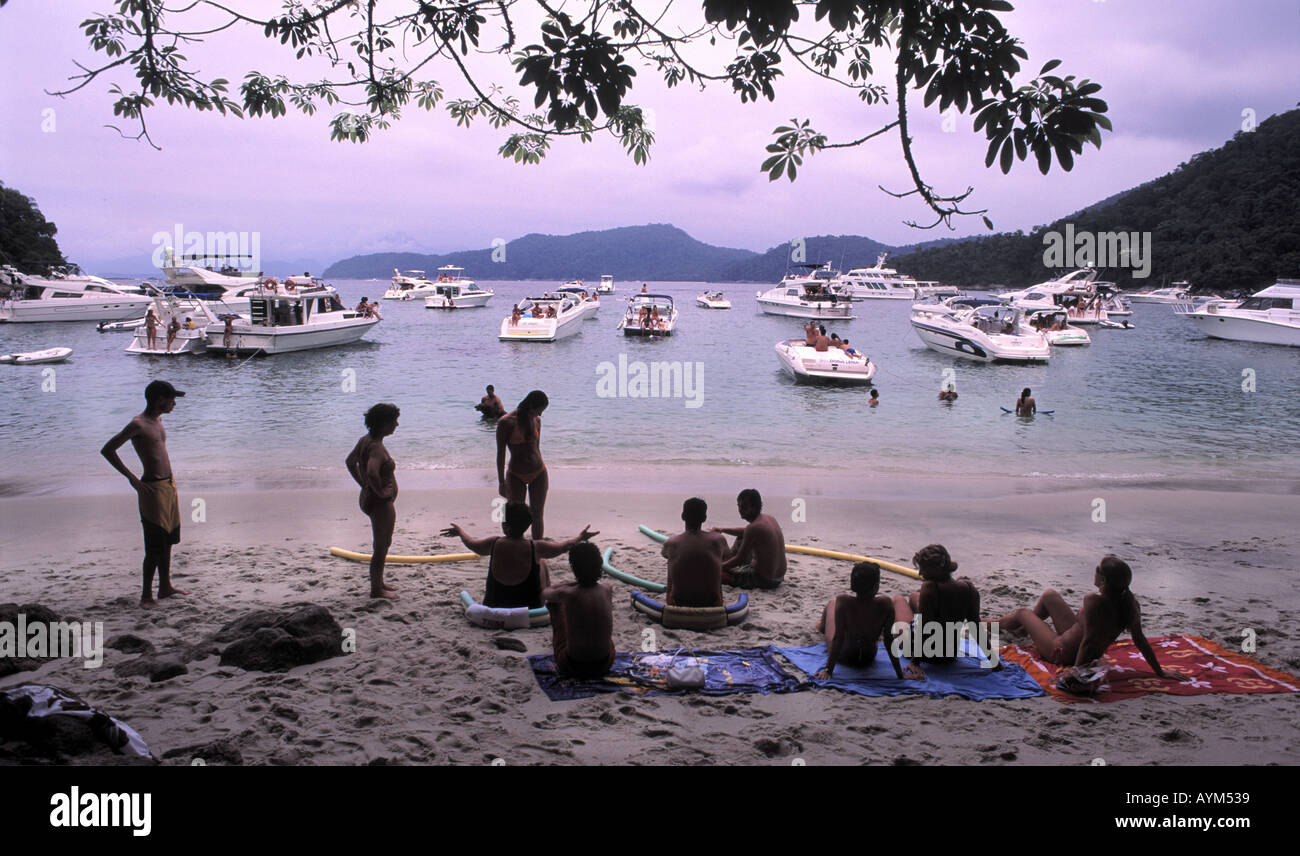 Wealthy Brazilians picnic on the beach with their luxury boats offshore at Ilha da Gipoia near Angra dos Reis - Stock Image
