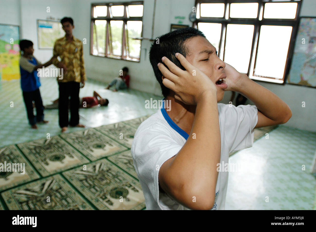 A young muslim boy in Banda Aceh Indonesia starts the midday prayer. Stock Photo