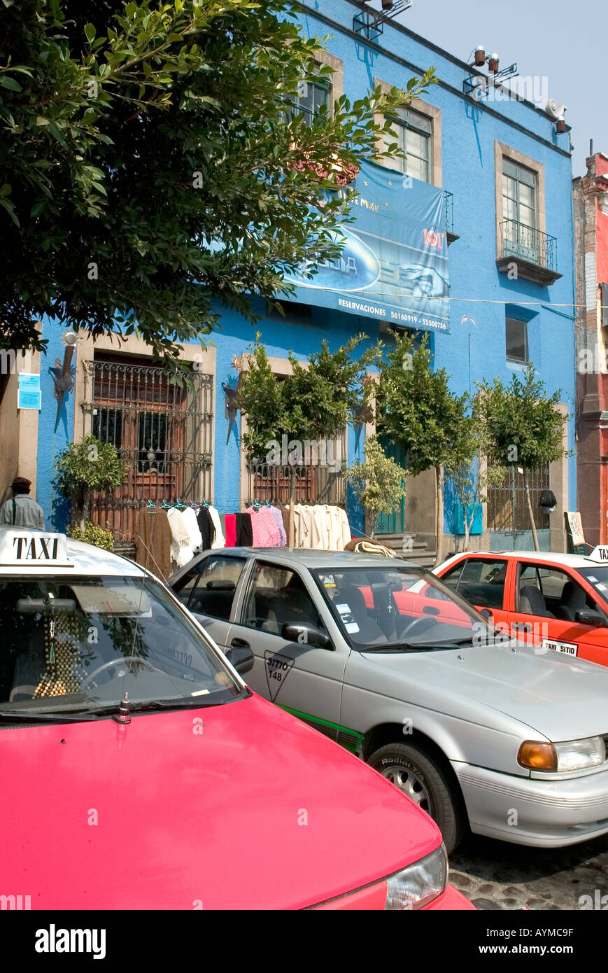 Taxi and cars parked infront of a bright blue building in San Angel Mexico City - Stock Image