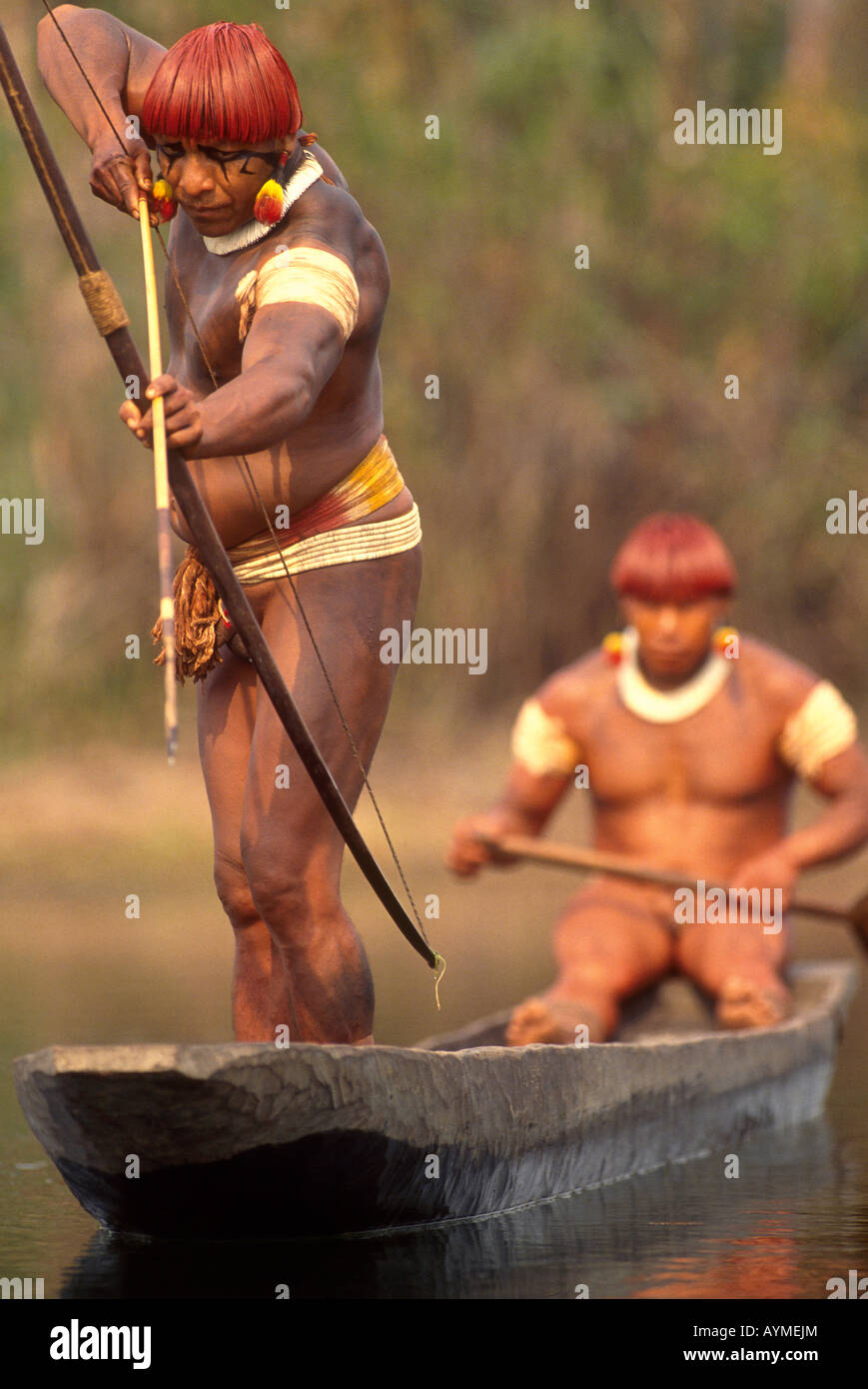 Xingu Amazon rainforest Brazil Yaulapiti indigenous People Indians in canoe fishing with bow and arrow - Stock Image