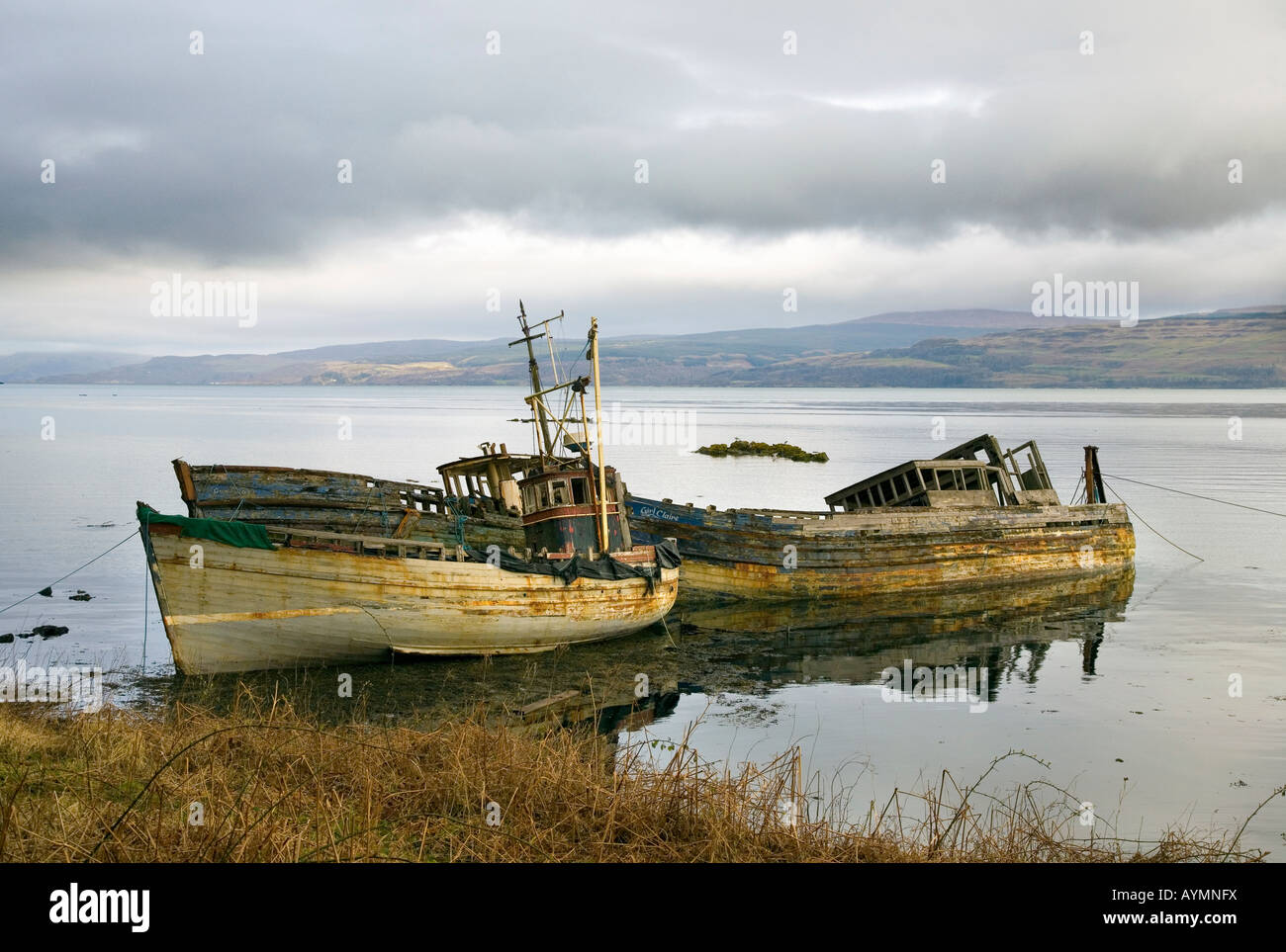 Two beached, Wrecked & Abandoned old wooden fishing boats on the beach at Salen, Isle of Mull, Argyll, Scotland Stock Photo